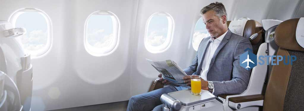 man reading newspaper on plane