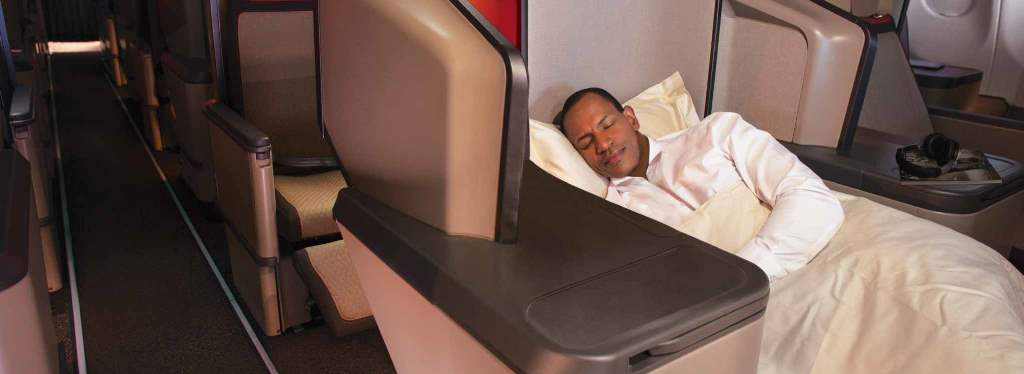 Man lying in Business Class seat.