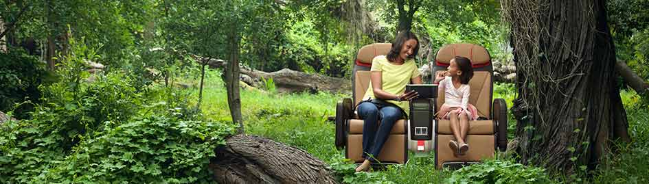 Woman and girl sitting in airplane seats in the woods