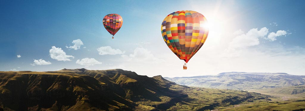 Hot air balloons flying over mountains