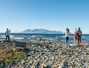 People overlooking the sea & Table Mountain