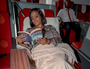 lady reading a book in business class seat